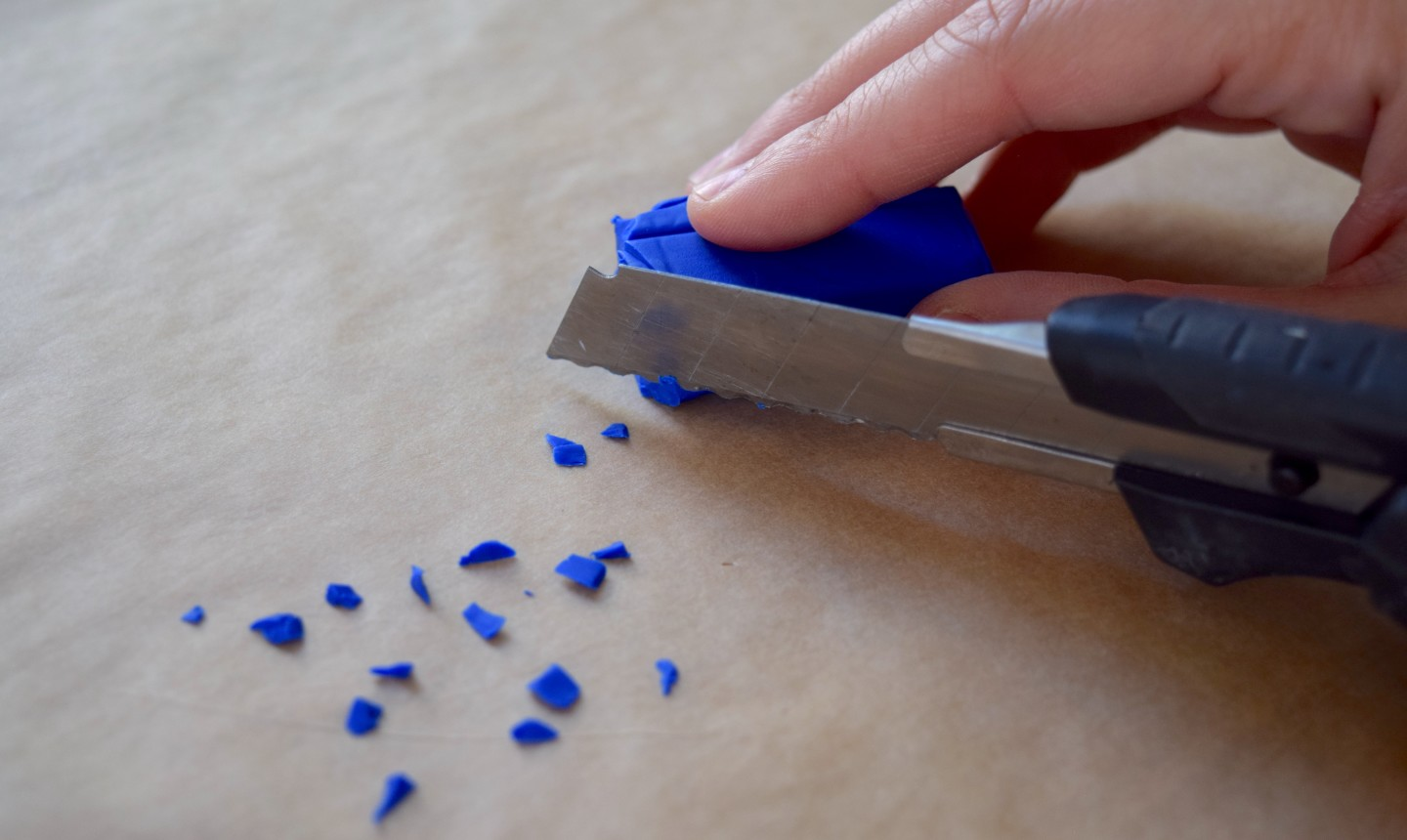 cutting small bits of blue clay