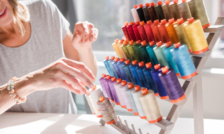 woman choosing thread from a thread stand