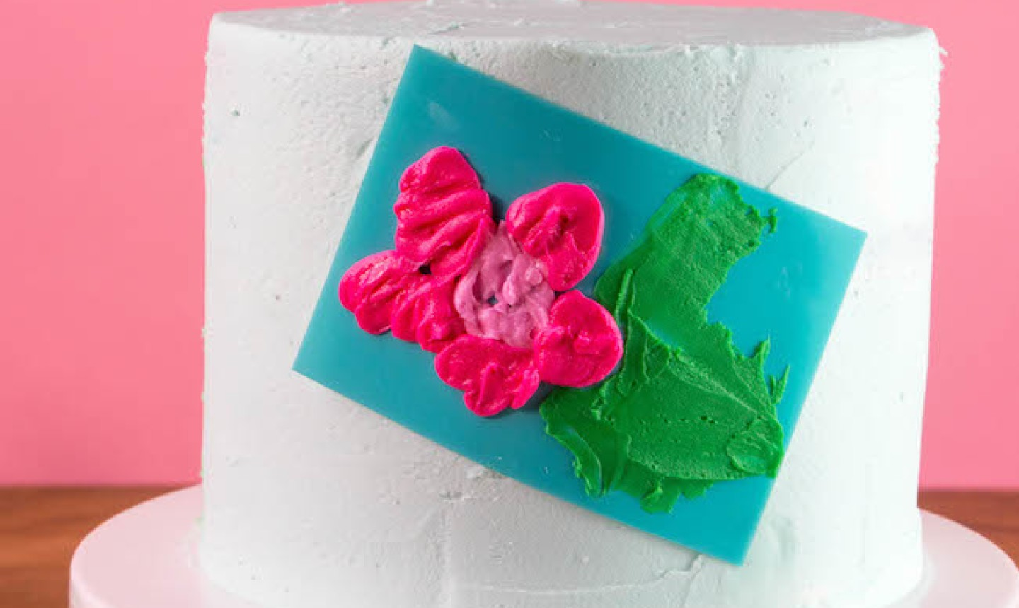 stenciling pink flower onto cake