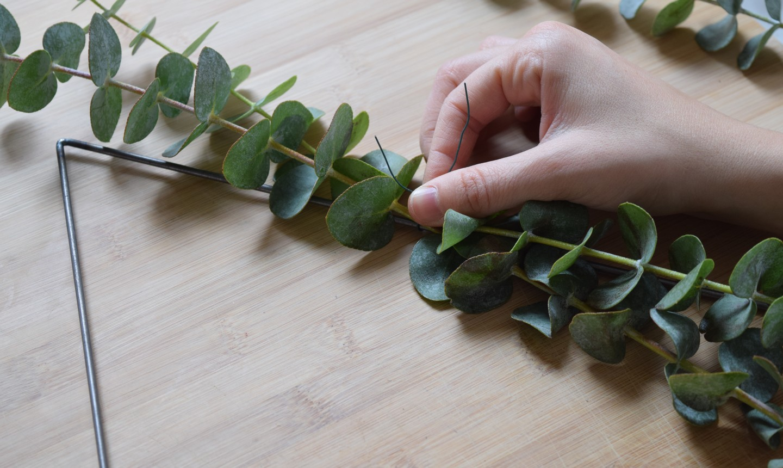 tying greenery to triangle wreath