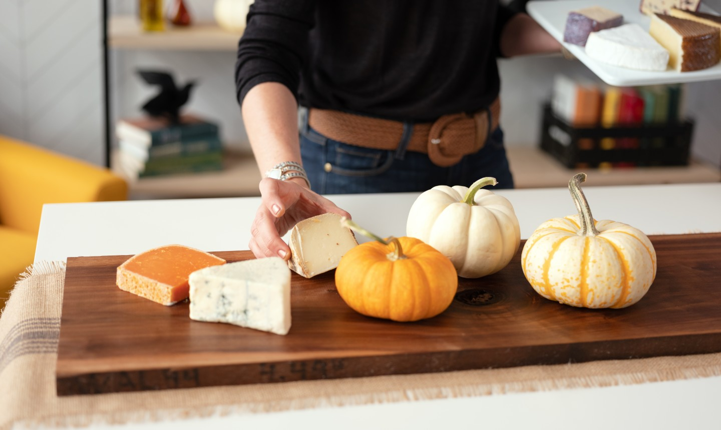 woman placing cheese on cheese board