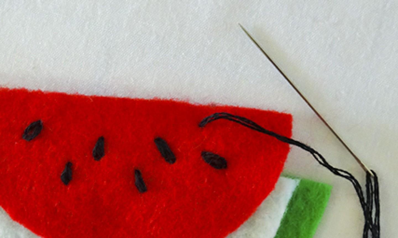 stitching watermelon seeds on felt