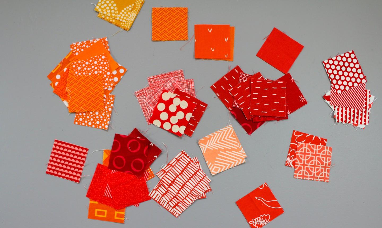 square scraps of red and orange fabric