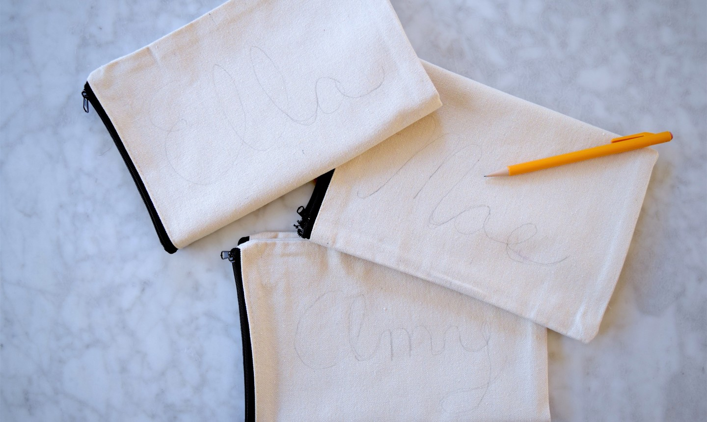 sketched names on canvas bags