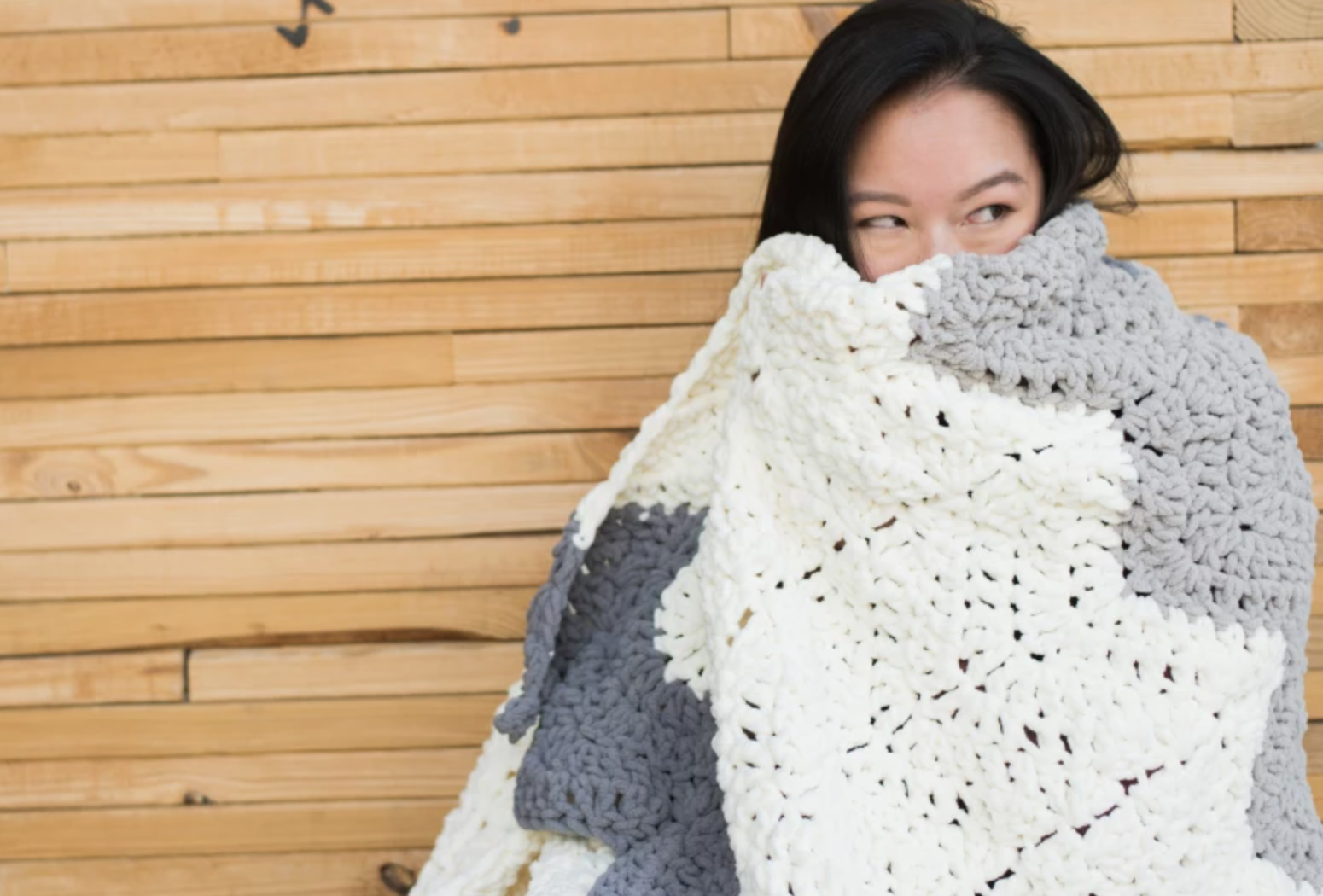 woman wrapped in crochet gray and white blanket