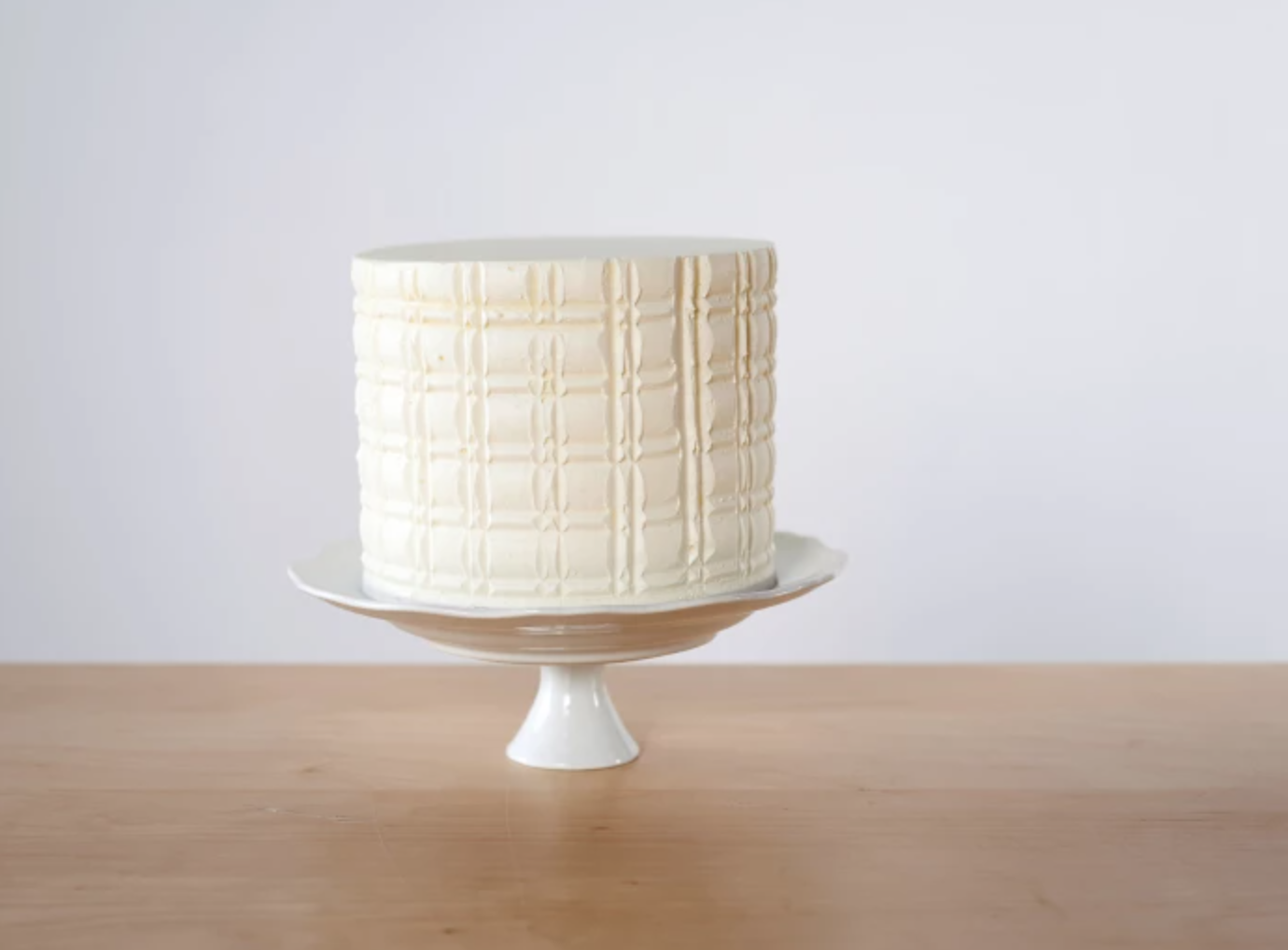 combed white cake on stand