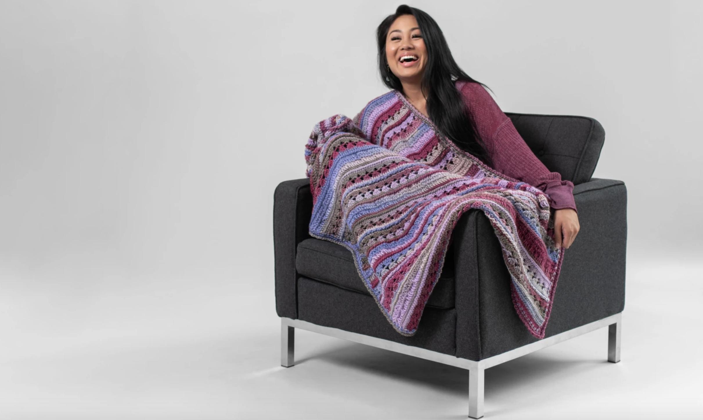woman with purple crochet blanket