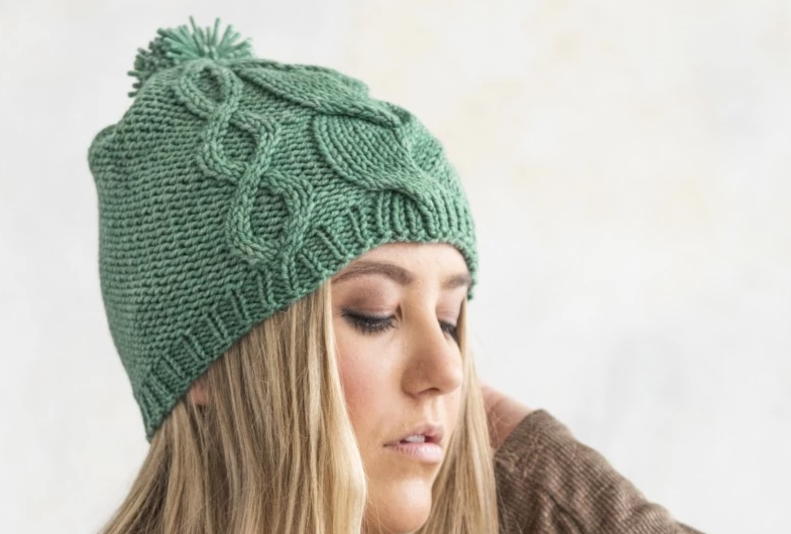 woman wearing green cabled knit hat