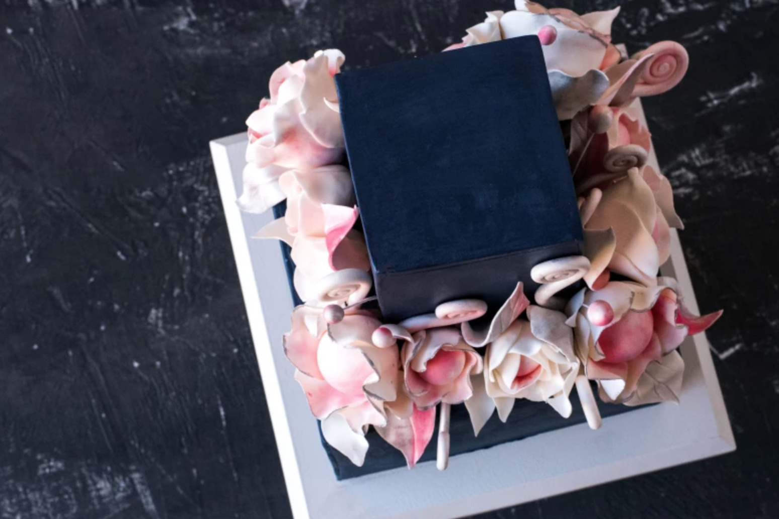 top view of pink white and black floral cake