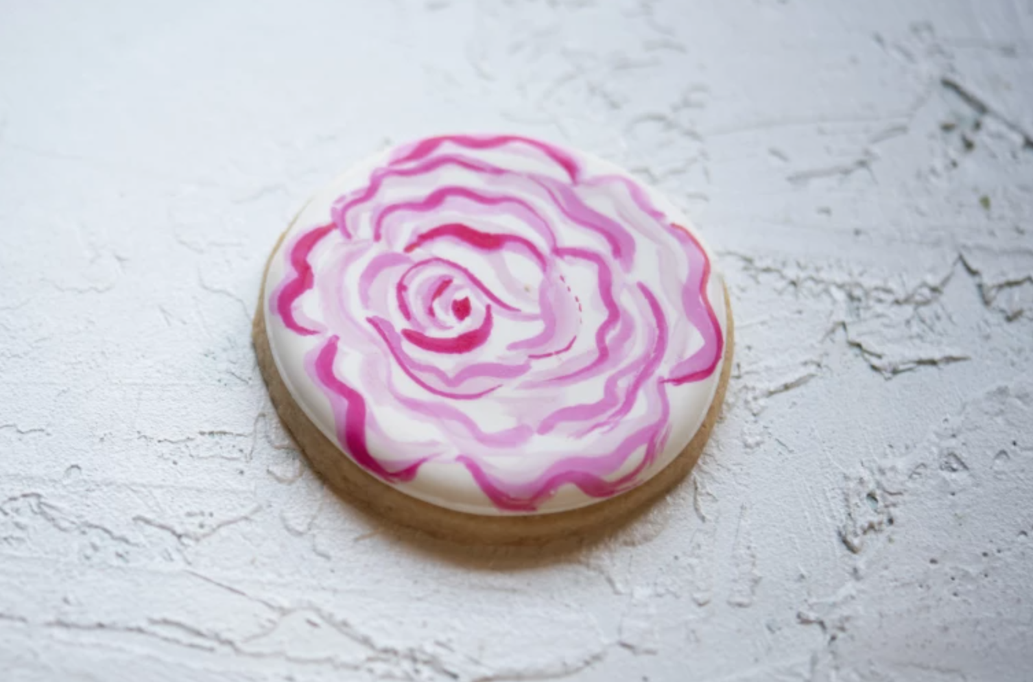 round sugar cookie with rose royal icing