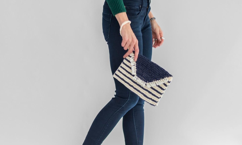 woman holding tunisian crochet clutch