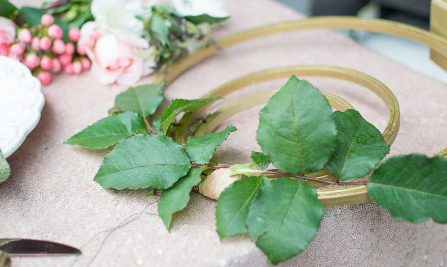 adding greenery to embroidery centerpiece