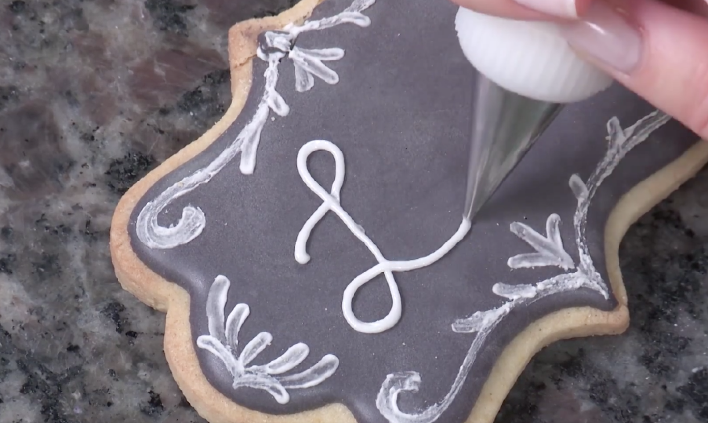 piping words on chalkboard cookie