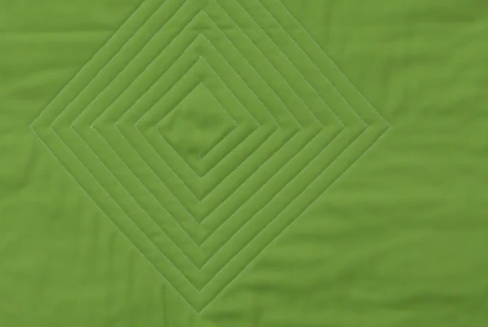 quilted diamond on green fabric
