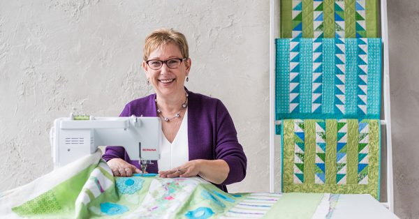 Woman sewing a quilt and smiling