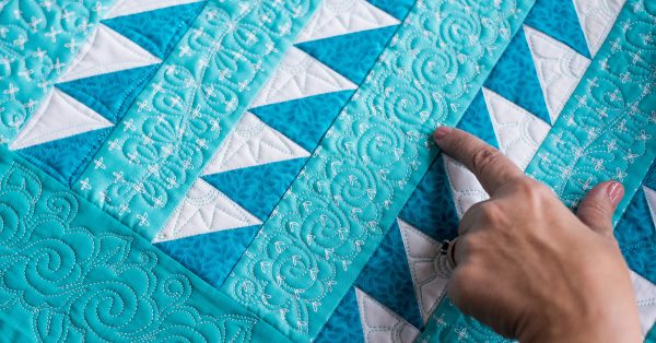 Person pointing to a blue and white quilt