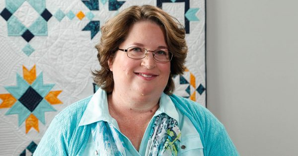 Woman in glasses in front of a quilt