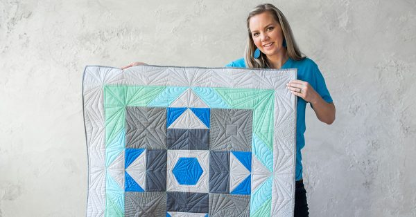 Woman holding up a blue, grey and green quilt