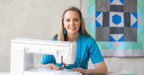 Woman smiling with a sewing machine