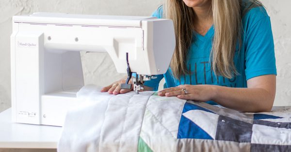 Woman in a blue shirt sewing a quilt