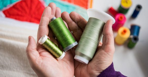 Person holding shades of green thread