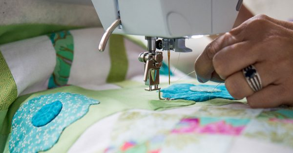 Sewing a scrap fabric flower to a quilt