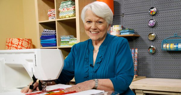 Woman smiling while using a sewing machine