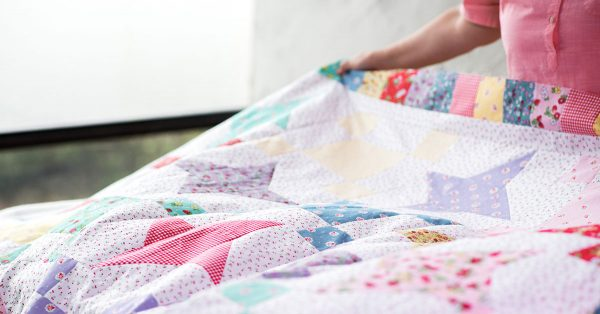 Person holding a colorful star quilt