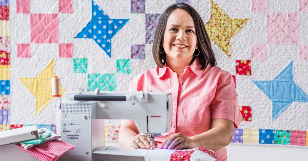 Woman using a sewing machine in front of quilt backdrop