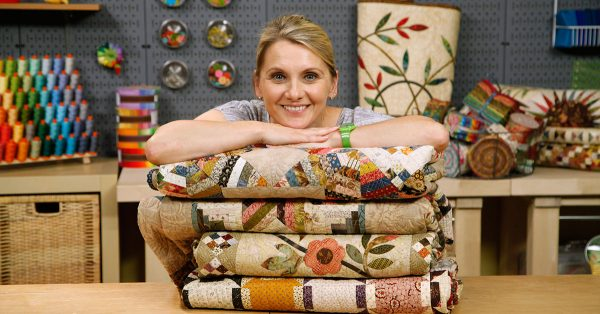 Woman smiling and posing on top of folded quilts