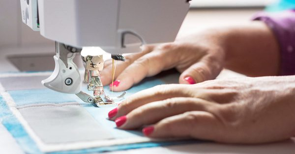 Person's hands using a sewing machine