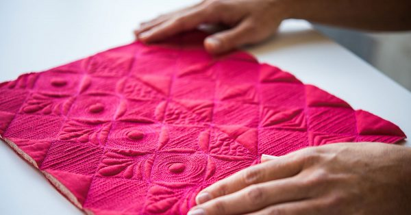 Person holding bright pink quilted square