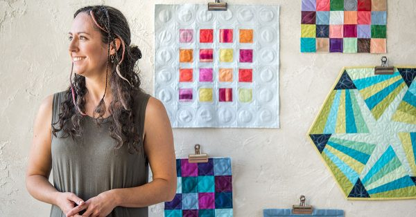 Woman standing on front of quilted blocks