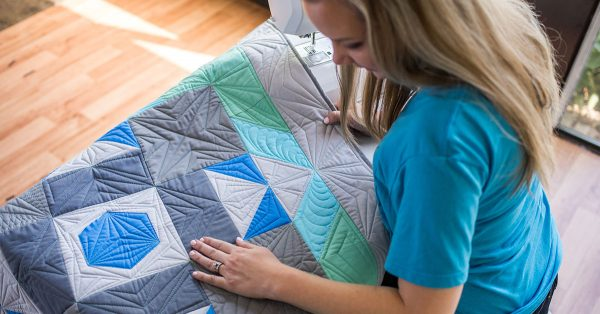 Woman looking at quilt with shades of blue and green