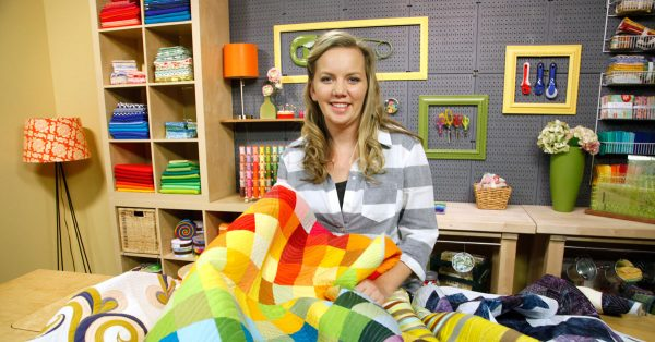Woman holding a rainbow quilt