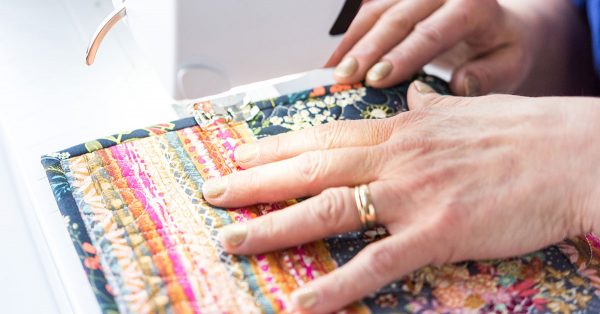 Person folding colorful quilted fabric