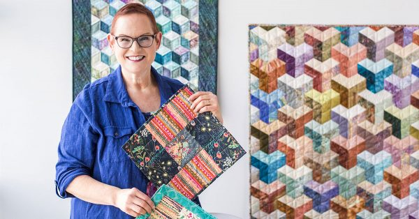 Woman holding up quilt squares