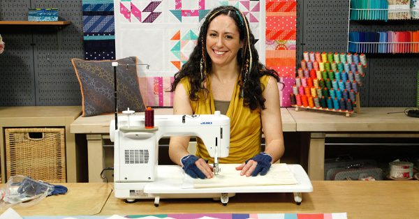 Woman smiling and using a sewing machine