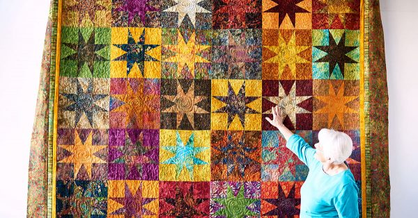 Woman touching star pattern quilt