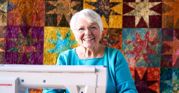 Woman smiling in front of a quilt background