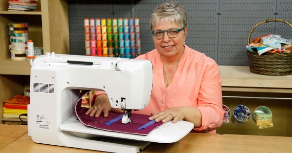 Woman in glasses sewing with a sewing machine
