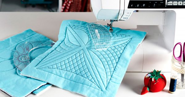 Blue quilt square on a sewing machine