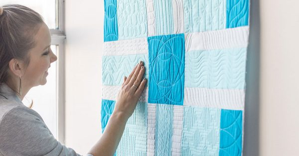 Person touching a blue and white quilt
