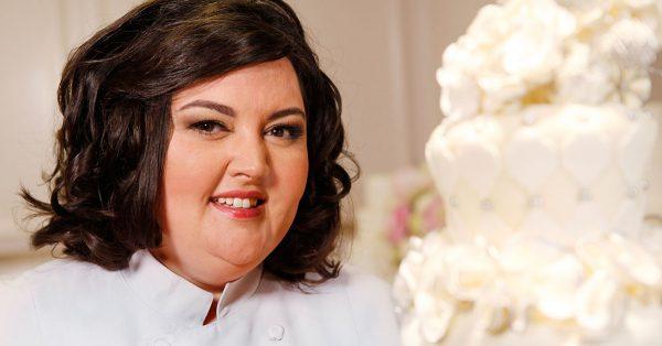 Woman smiling near a white cake