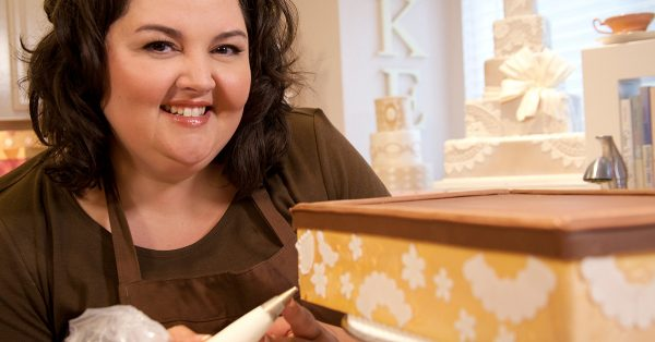 Woman piping frosting designs on a cake
