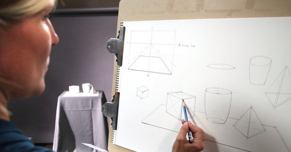 Person drawing 3D shapes with a pencil