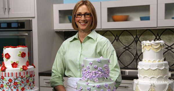 Woman standing in front of three decorated cakes