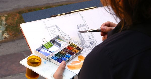 Person holding a water color paint tray