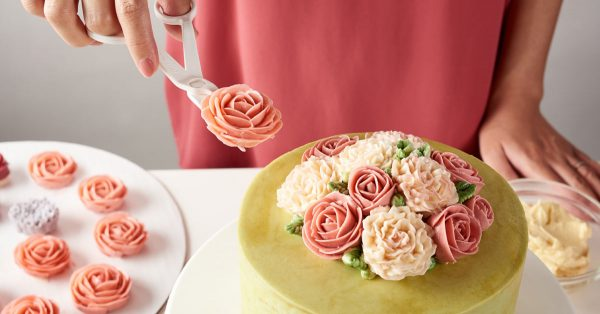 Adding buttercream flowers to a cake