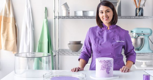 Woman in a purple chef coat with a purple cake